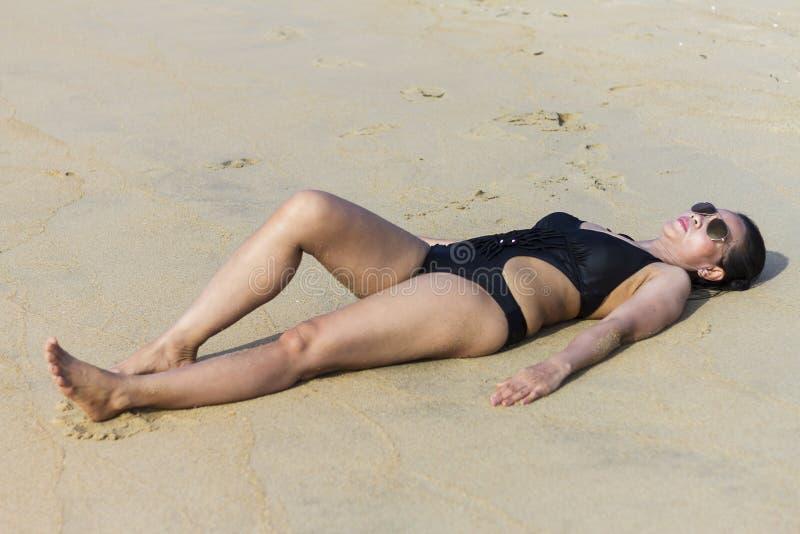 Sexy Damenkörper entspannen sich auf Sand lizenzfreies stockfoto