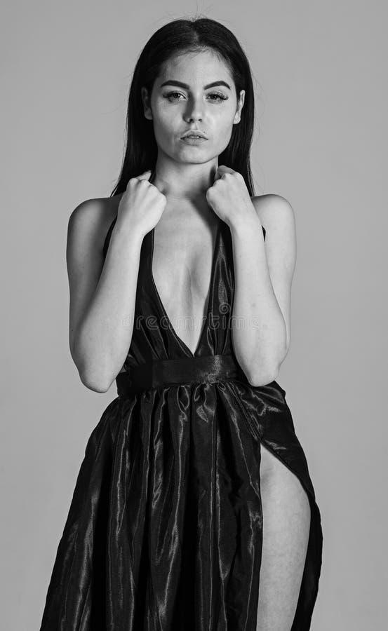 Sexy decolleteconcept Vrouw in elegante zwarte avondjurk met decollete, grijze achtergrond Het aantrekkelijke meisje draagt royalty-vrije stock fotografie