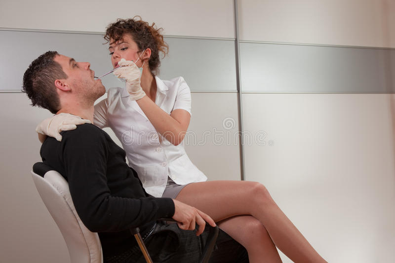 Dentist. Young female dentist taking care about her patient stock photo