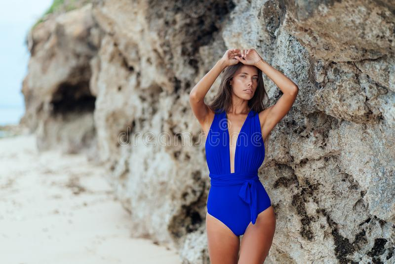 Sexy donkerbruin meisje in blauwe swimwear rust op wit zandstrand royalty-vrije stock foto