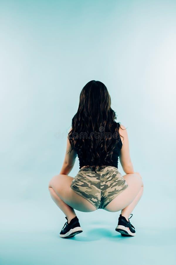 Sexy donkerbruine vrouw die twerk op blauwe achtergrond, erachter dansen van stock afbeelding