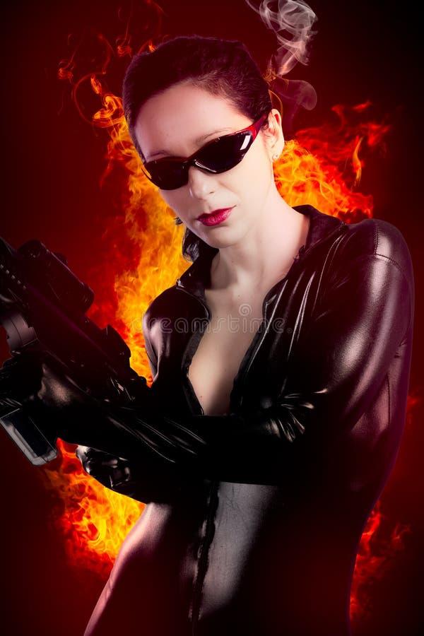 Sexy donkerbruine vrouw in latex jumpsuit met zwaar kanon over brand   stock fotografie