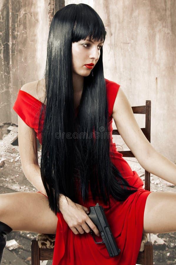 Sexy donkerbruine vrouw in rode kleding met wapen royalty-vrije stock foto's