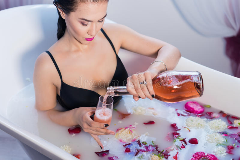 Sexy donkerbruine vrouwen gietende champagne in bad stock afbeeldingen