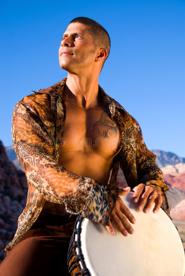 Drum player. Muscular man with his shirt open playing a drum outside. Looking towards the sun royalty free stock photos