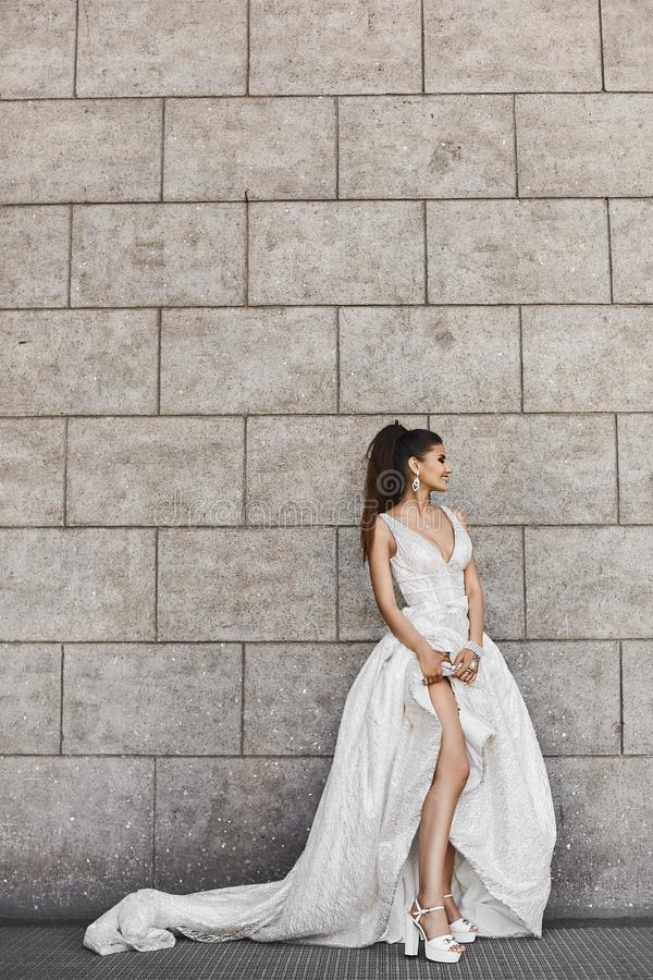 and elegant brunette model girl in a bright beige dress lifted the hem of the dress and bare her long legs stock image