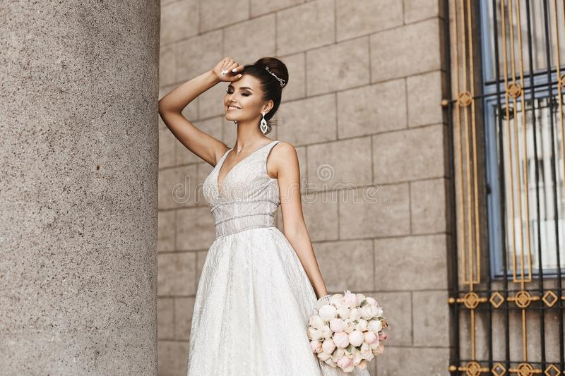 and elegant brunette model girl with bright makeup and stylish hairstyle, in a fashionable beige dress with bouquet of flower royalty free stock image