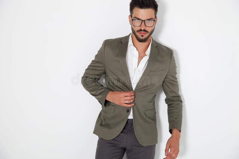 Elegant man buttoning his coat. On looks to the camera on white background royalty free stock photo