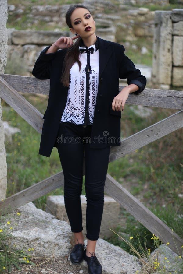 elegant woman with dark hair wears white shirt and black pants stock photos
