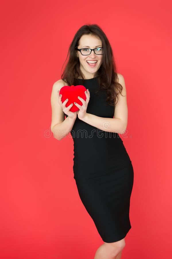 Sexy elegant woman hold red valentines day heart. formal woman in glasses. businesswoman in black dress. party royalty free stock images