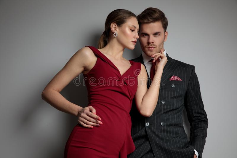 Elegant woman touching man`s face with her fingers. Elegant women touching her her man`s face with her fingers on grey background stock photography
