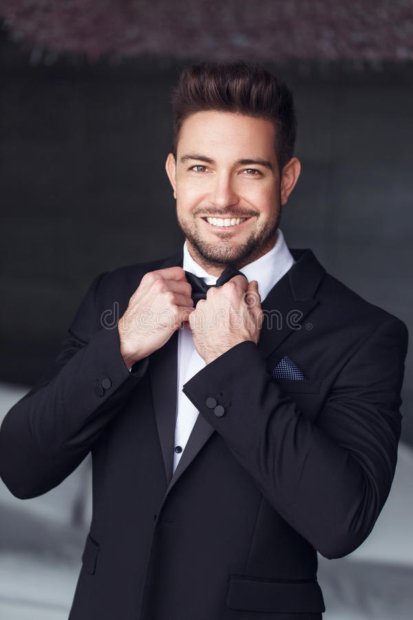 Elegant young macho man tie a bow. Elegant young caucasian macho man tie a bow royalty free stock photography
