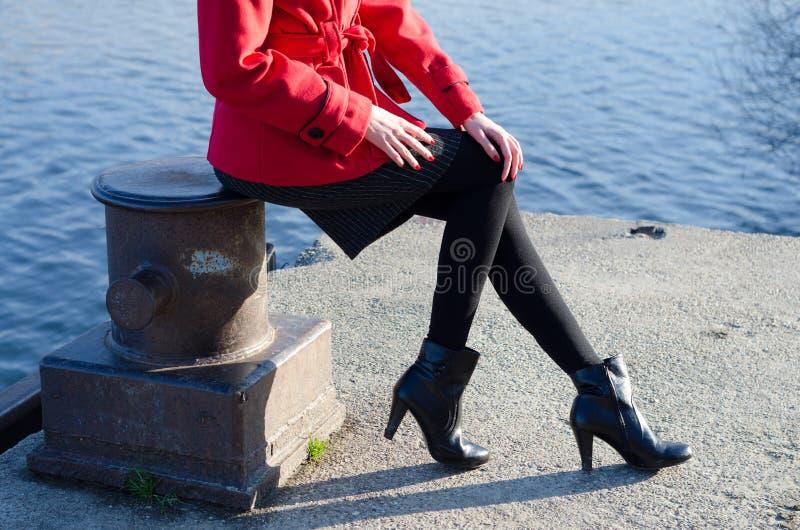 Sexy elegante moderne Dame, die neben Fluss sitzt lizenzfreie stockbilder