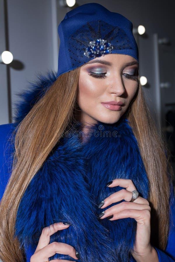 Sexy elegantes Mädchen der schönen Mode mit modischer blauer Kappe des langen Haares auf seinem Kopf vom Abend helles Make-up sit stockfoto