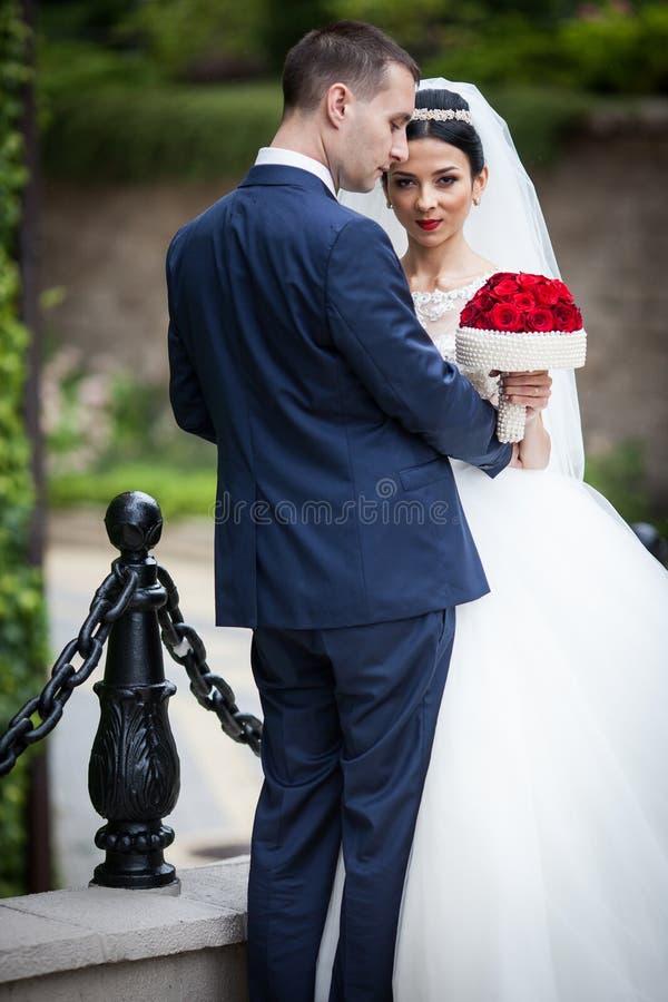 Sexy emotionale Brunettebraut, die Bräutigam umarmt und Blumenstrauß hält lizenzfreie stockbilder
