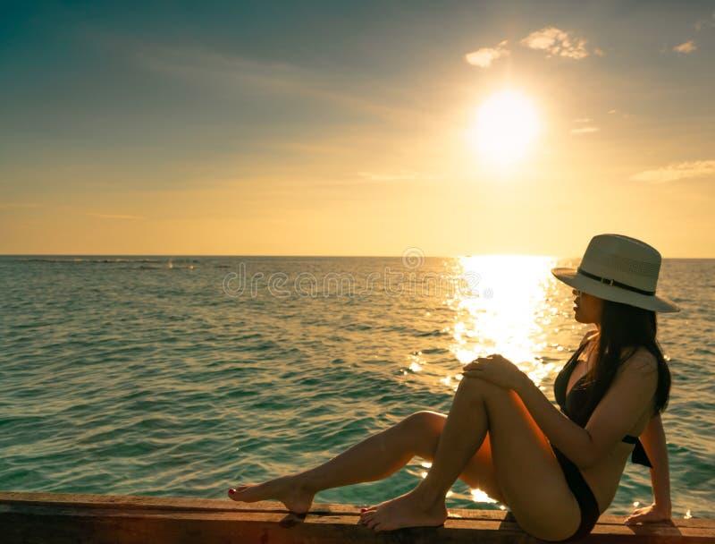 Sexy en ontspan vrouwenslijtage de zwarte bikini met strohoed op houten straal dichtbij zandstrand bij zonsondergang zit Het meis royalty-vrije stock foto