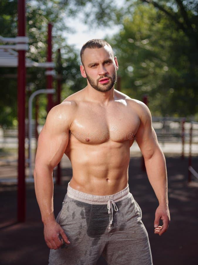 Sexy en spier shirtless bodybuildermens die op een vage achtergrond pronken met Het uitwerken van concept stock foto
