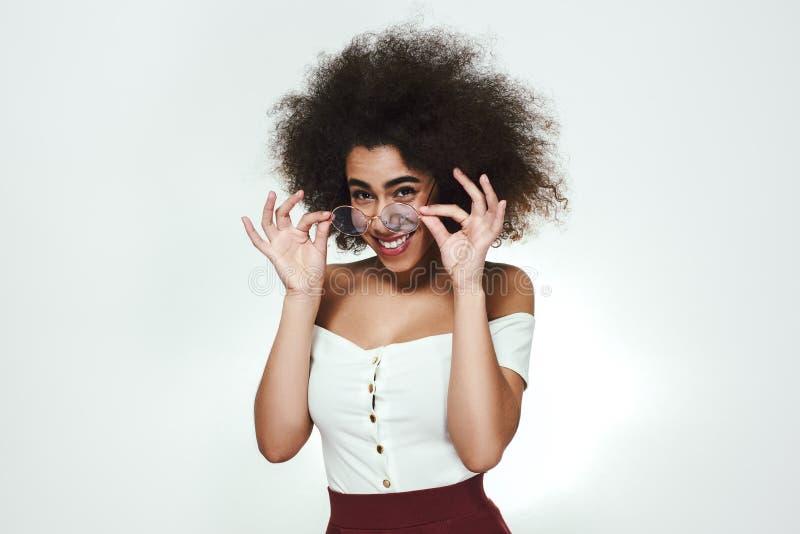 Sexy et futé Jeune femme afro-américaine attirante ajustant son eyewear et regardant la caméra avec le moment de sourire photographie stock