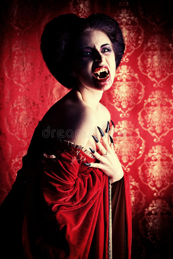Evil. Portrait of a bloodthirsty female vampire over red vintage background stock photos