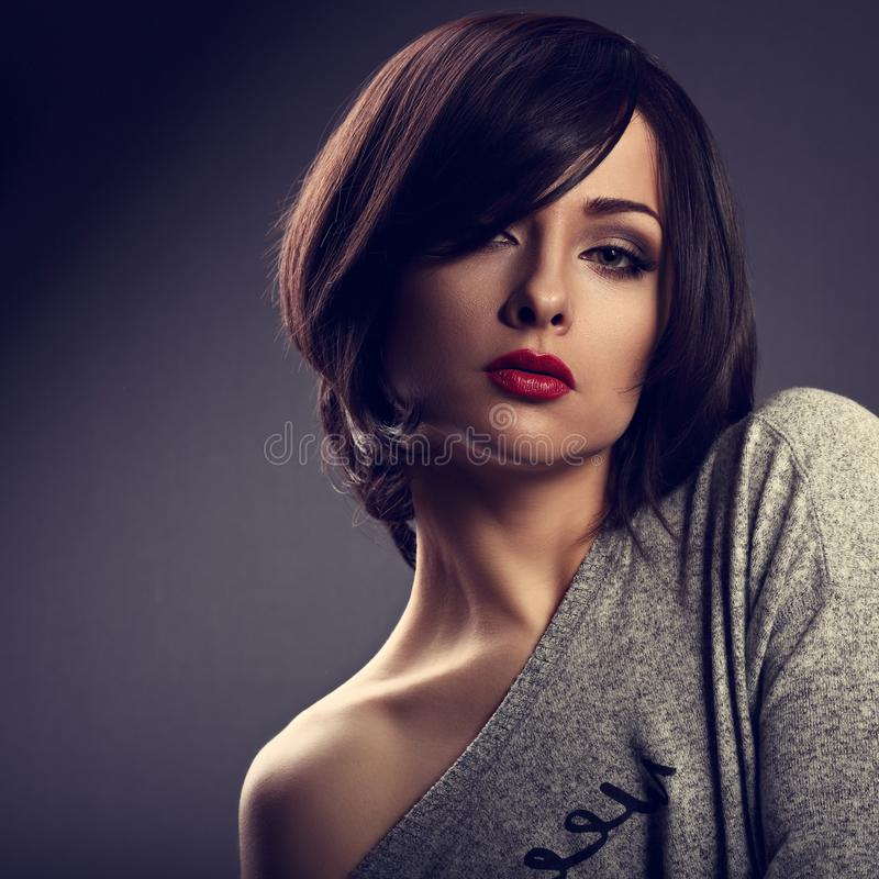 Expressive makeup woman with short bob hair style, red lips. Tick on dark shadow background. Closeup toned portrait stock photos