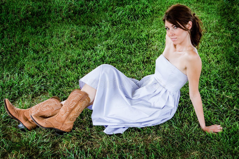 Farmgirl Fashion Model. Beautiful and girl with a cowgirl / farmgirl / girl next door fashion laying back in the green grass. Flirty Smile stock images
