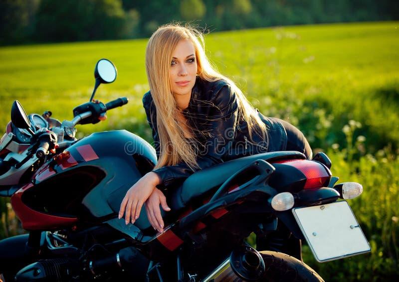 fashion female biker girl. Blonde woman in leather jacket sitting on vintage custom motorcycle. Outdoors lifestyle stock image
