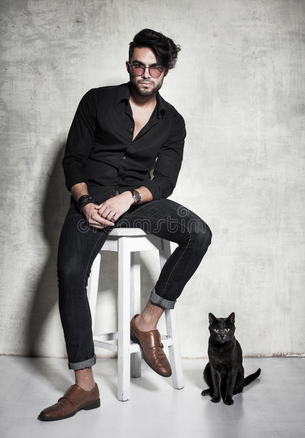 fashion man model dressed casual posing with a cat against grunge wall stock photo