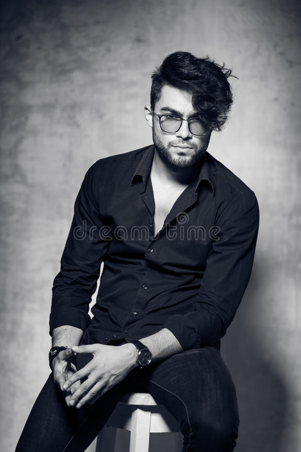 fashion man model dressed casual wearing glasses posing dramatic against grunge wall stock photo