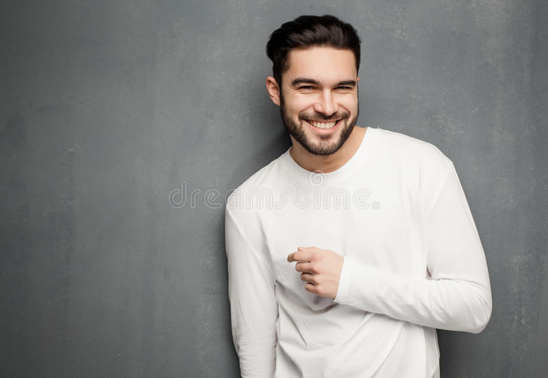 Fashion man model in white sweater, jeans and boots smiling against wall. Fashion man model in white sweater, jeans and boots posing royalty free stock photos