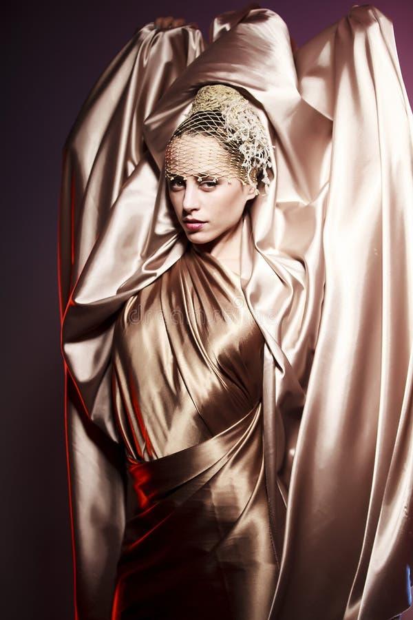 Fashion woman. Woman with golden silk sheet stock image