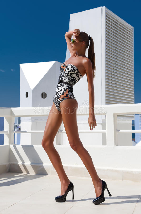 fashion woman with long legs in swimsuit, in shoes, outdoor royalty free stock image