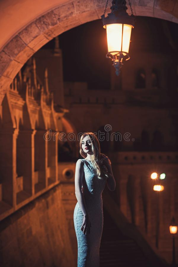 Sexy fashionable beautiful young woman in long evening dress over view on night city lights. Pretty lady with long hair. Sexy fashionable beautiful young woman royalty free stock image