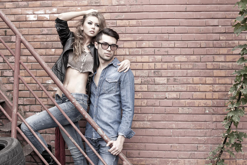 and fashionable couple wearing jeans dramatic stock photo