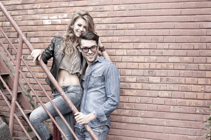 and fashionable couple wearing jeans smiling stock photography