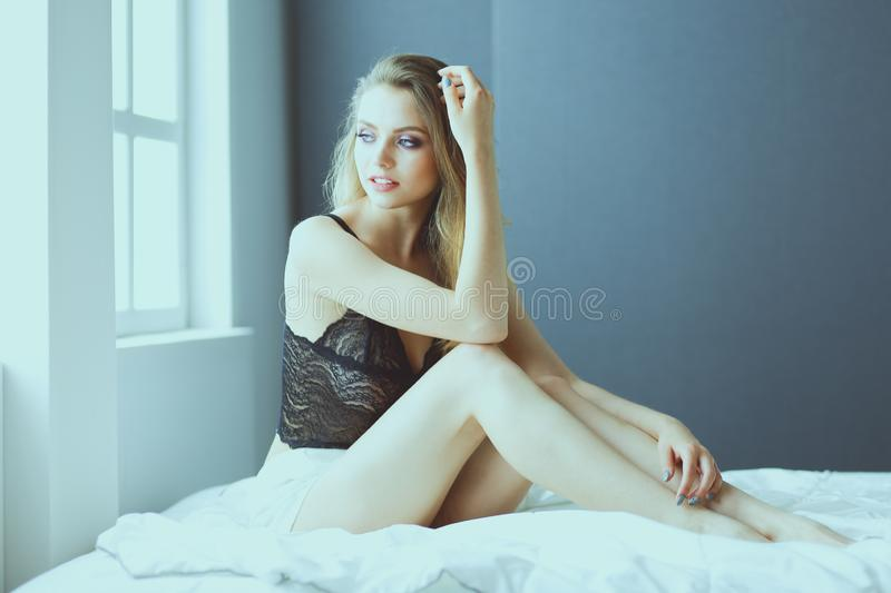 Sexy fashionable woman on the bed stock photo