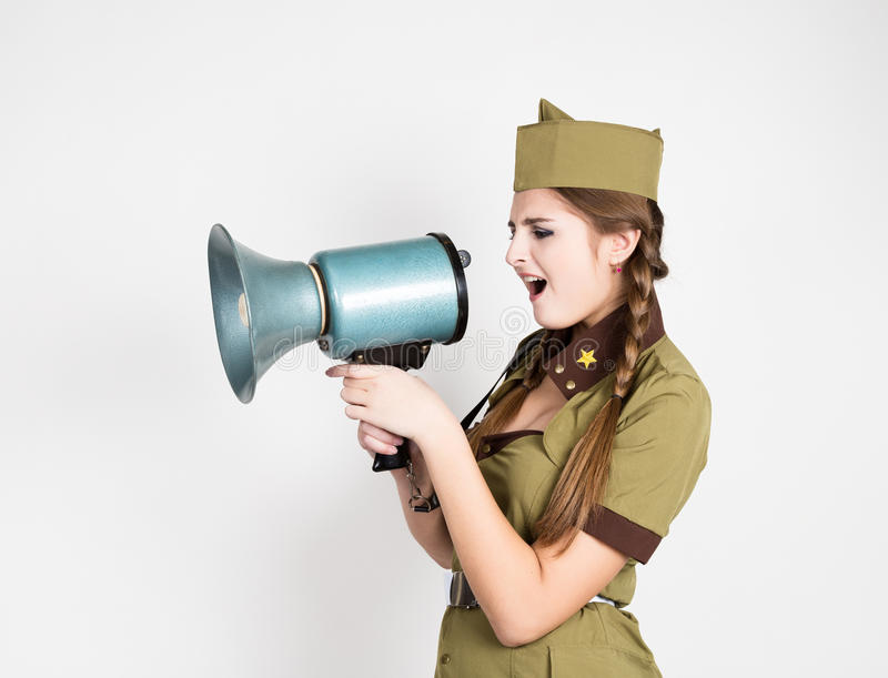 Fashionable woman in military uniform and garrison cap, holding bullhorn and screaming. Fashionable woman in military uniform and garrison cap,holding bullhorn royalty free stock image