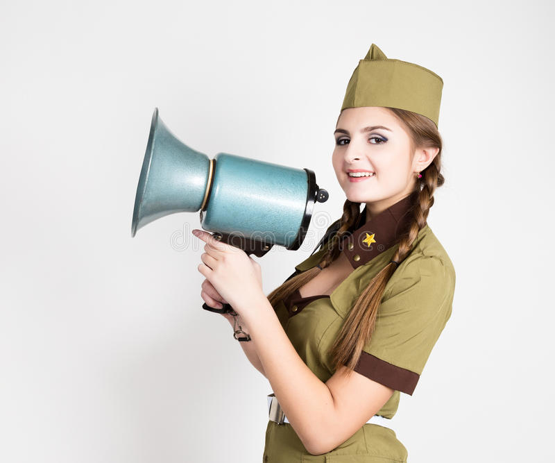 Fashionable woman in military uniform and garrison cap, holding bullhorn and screaming. Fashionable woman in military uniform and garrison cap,holding bullhorn royalty free stock images