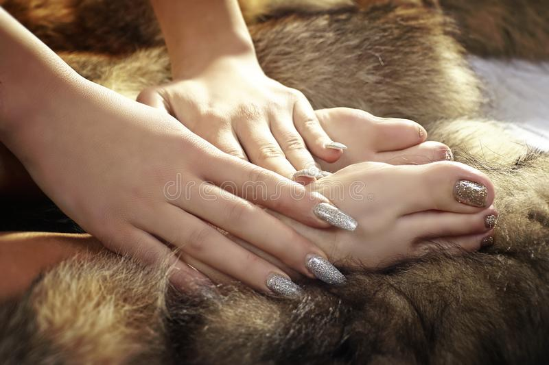 Toes and Fingers in Fur. Feet caressed by beautifully manicured hands bedded in coyote pelts stock photo