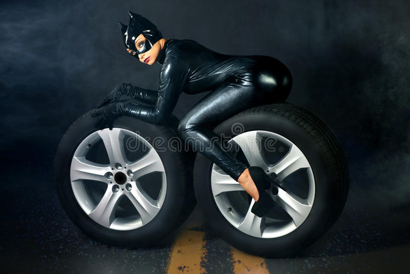Female in black catwoman costume. On motorcycle stock photography