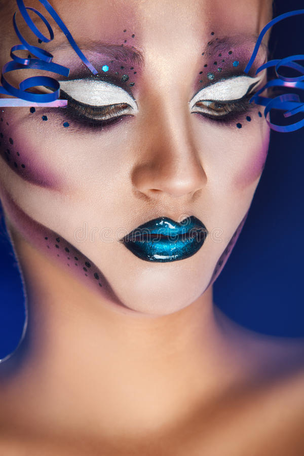 Female with creative make up in studio. On blue background stock image
