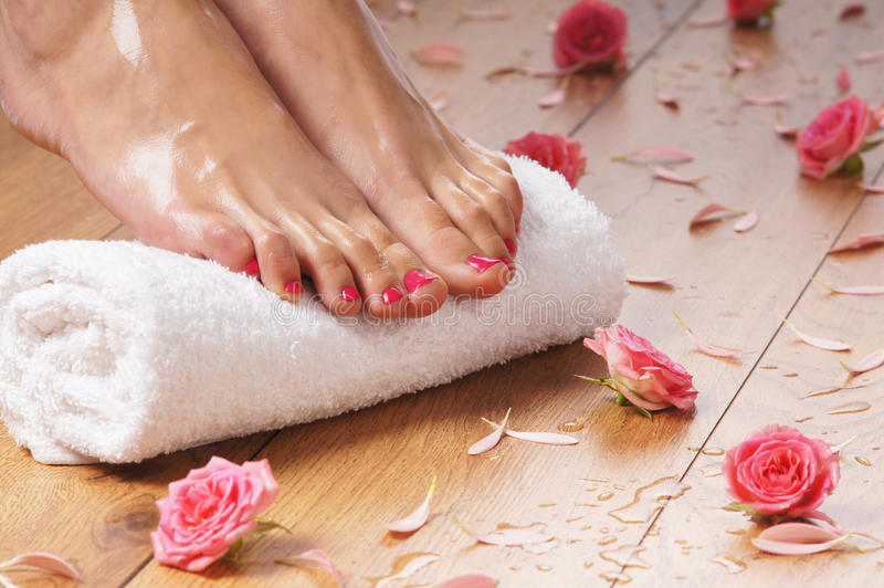 female feet, a white towel and petals on the floor royalty free stock image