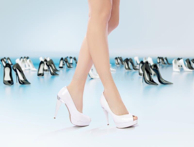 Female legs among high-heel shoes. Female legs among lots of high-heel shoes royalty free stock photo