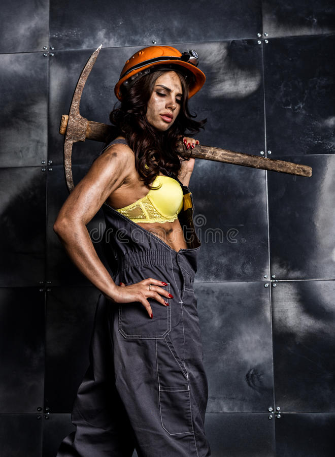 Female miner worker with pickaxe, in coveralls over his naked body.  stock photo