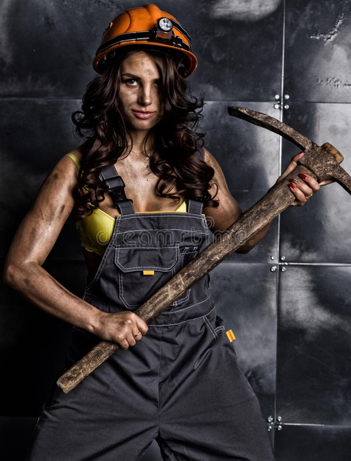Female miner worker with pickaxe, in coveralls over his naked body.  stock images