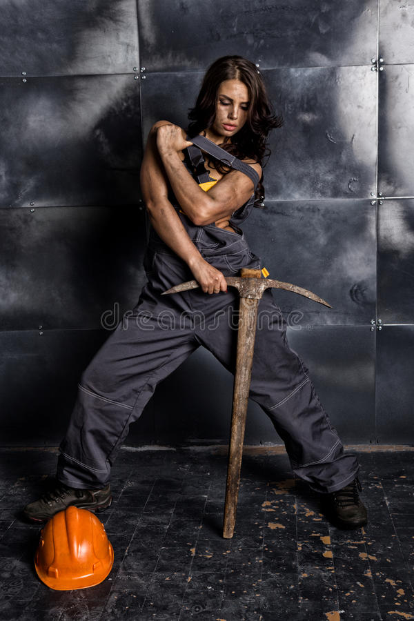 female miner worker with pickaxe, in coveralls over his naked body. erotic industry concept stock photos