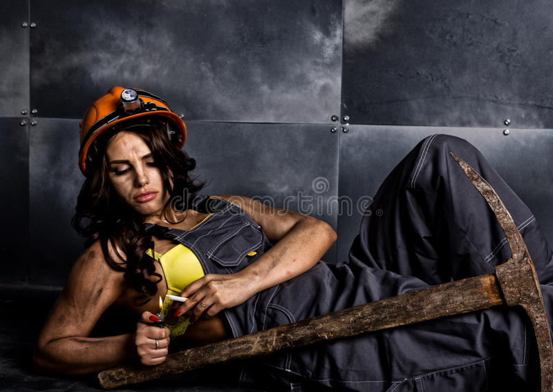 Female miner worker with pickaxe, in coveralls over his naked body, sitting on the floor on backdrop of steel wall.  stock photo