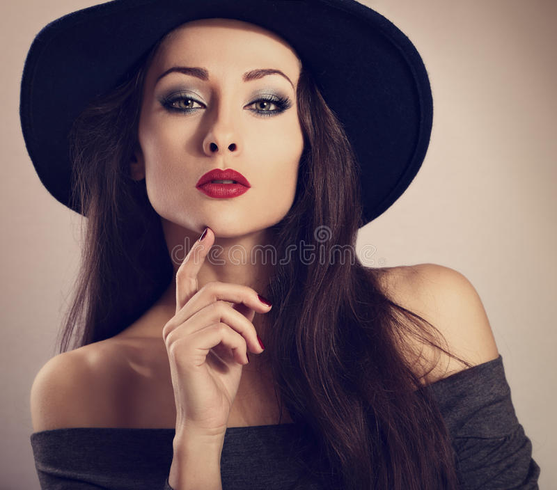 Female model with bright makeup and red lipstick in black h. At posing with expressive look. Closeup fashion portrait. Toned closeup retro portrait royalty free stock image