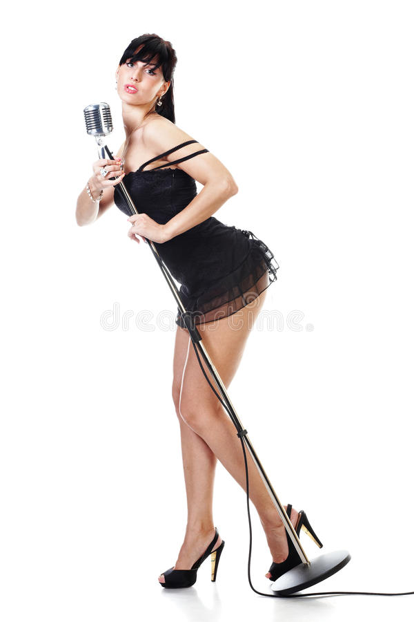 Female singer wearing black dress holding a r. Etro microphone isolated on white stock photo