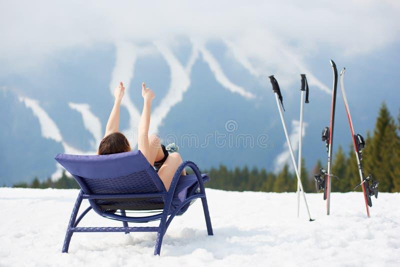 female skier on blue deck chair near skis at ski resort stock image