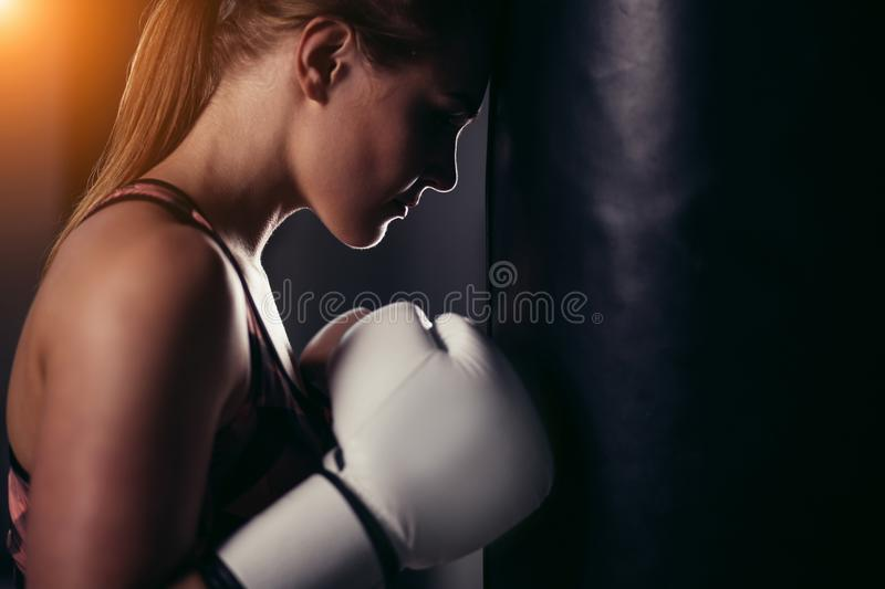 Fighter girl in gym with boxing bag. Long hair woman fitness model. Resting after boxing royalty free stock photo